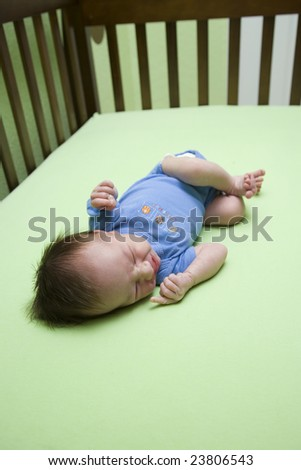 A week old baby in a crib. Shallow DOF - stock photo