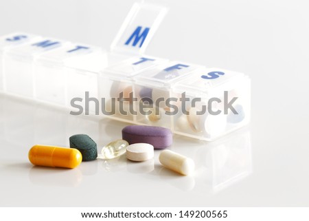 A weekly container of tablets, vitamins etc. on white reflective ceramic surface - stock photo