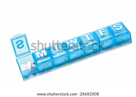 A weeks' worth of medication in a blue pill box. - stock photo