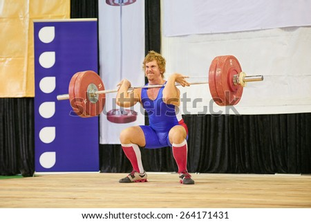 A weight lifter lifting weights during a competition - stock photo