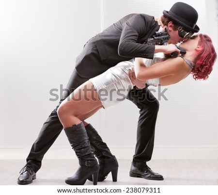 a weird couple of strange business superheroes in which she loves and hates him and they are attracted and the have to kill each other - stock photo