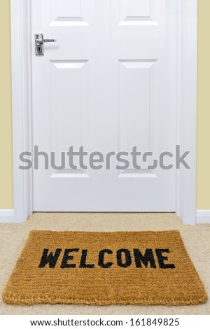 A Welcome doormat in front of a door. - stock photo