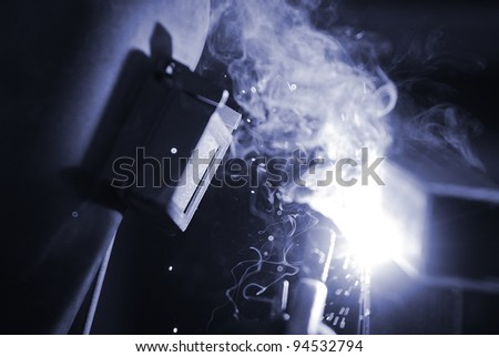 a welder in a safety mask welds, blue toning - stock photo