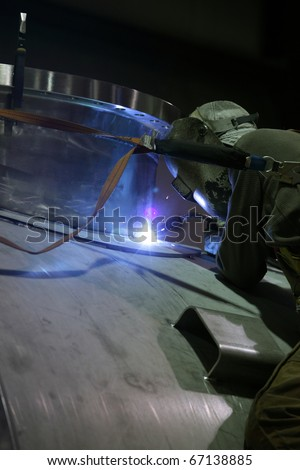 A welder welding a port on a pressure vessel.