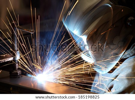 A welder welding the top on a pressure vessel. - stock photo