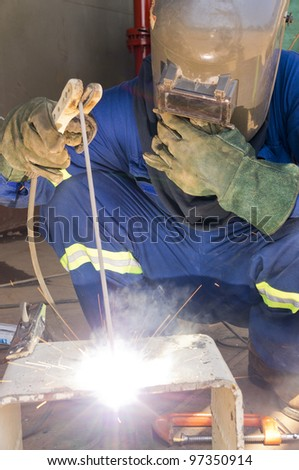 A welder with personal protective equipment welding the steel bracket - stock photo