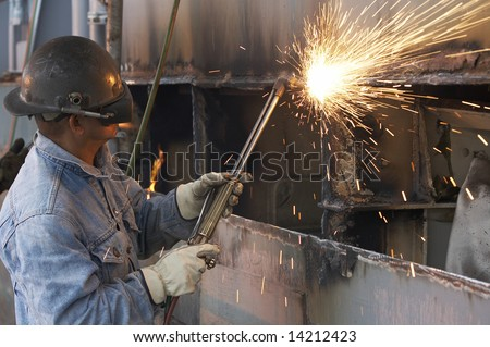 a welder working a torch at shipyard - stock photo