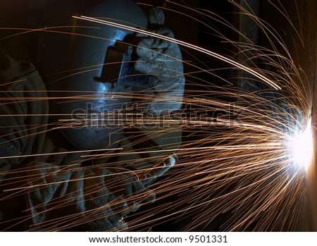 a welder working at shipyard at night - stock photo