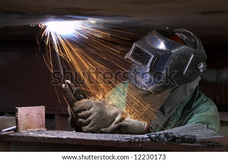 a welder working at shipyard during night shift - stock photo