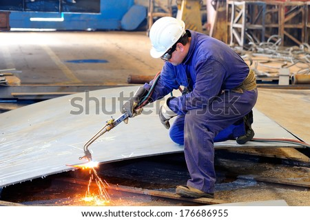 a welder working at shipyard in day time - stock photo