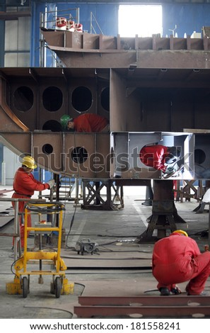 A welder working at shipyard in day time. - stock photo