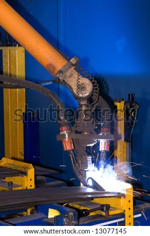 A welding robot, equipped with two torches, welding two steel parts together