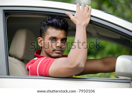 A well-built Asian man in a saloon car in the country