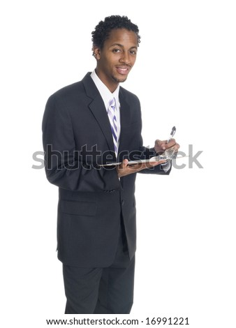 A well dressed African American businessman writing on a clipboard while smiling.