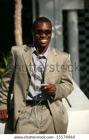 a well dressed african american Male Model listens to his personal digital music player - stock photo