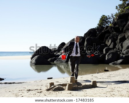 A well dressed businessman showing his legs about to step on a beautifully made sand castle, whilst still holding the red plastic bucket and spade.