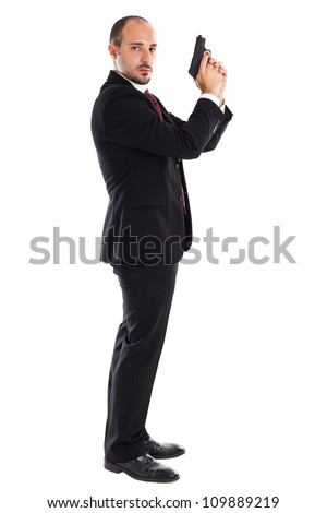 a well dressed businessman with a gun posing like a secret agent - stock photo