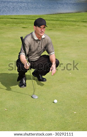 A well-dressed male golfer sizing up his next putt. - stock photo