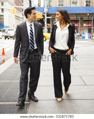 A well dressed man and woman walk down a city street.