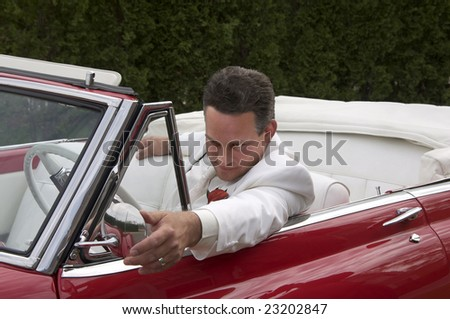 A well dressed man in a classic red convertible.