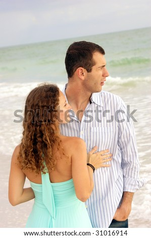 A well dressed young couple  with their bodies facing each other, both are looking out at the ocean to the right. Shot at a slight angle - stock photo
