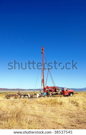 A well drilling rig in an empty field. - stock photo