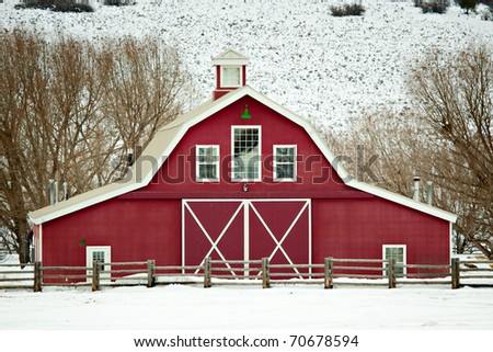 A well-kept, classic red barn in a rural winter setting in Utah, USA. - stock photo