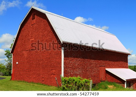 A well maintained red barn in summer - stock photo