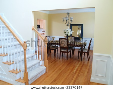 A well staged dining room viewed from the foyer with the staircase in the foreground - stock photo