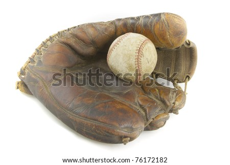 A well-used baseball sits in a vintage baseball glove. - stock photo