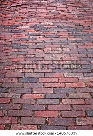 A well-weather brick path heads into the distance - stock photo