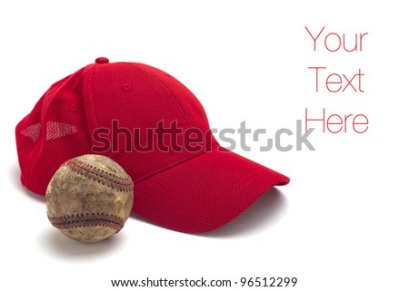 A well worn baseball and a red cap isolated on a white background, copy space - stock photo