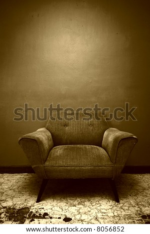 A well worn chair set against a wall in a room in Mexico.