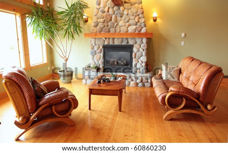 A west coast living room with a river rock fireplace. - stock photo