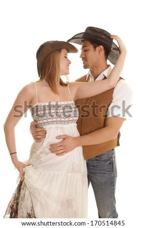 A western couple are smiling and wearing cowboy hats. - stock photo