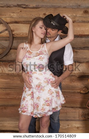 A western couple is standing together and she is holding his hat. - stock photo
