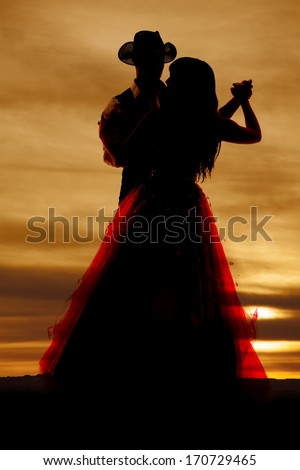 A western silhouette of a couple dancing together. - stock photo