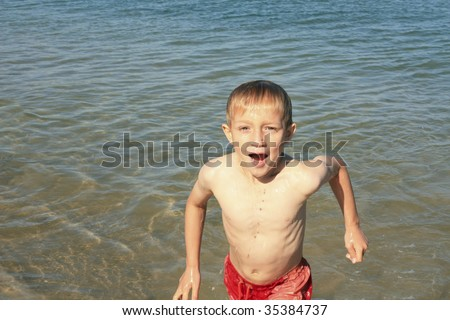 a wet boy coming out of the sea having been completely immersed