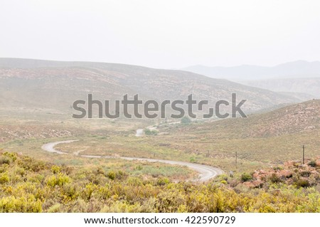 A wet Nuwekloofpas (new valley pass) descending into the Baviaanskloof (baboon valley) during a rain storm - stock photo
