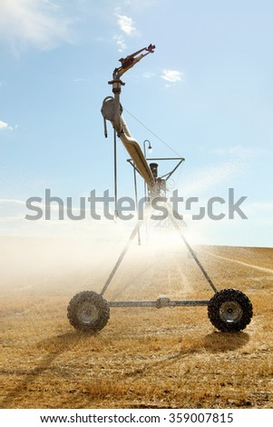 A wheel line used to irrigate a wheat field. - stock photo