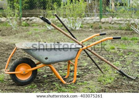 a wheelbarrow with a rake - stock photo