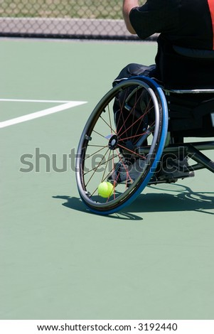 A wheelchair bound athlete on the tennis court - showing the angle of the wheel and the tennis ball being held in - stock photo