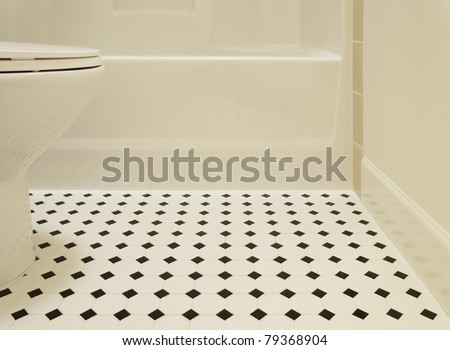 A white acrylic bathtub and porcelain toilet of a bathroom are sitting on a diamond patterned vinyl flooring in a bathroom. Horizontal shot. - stock photo