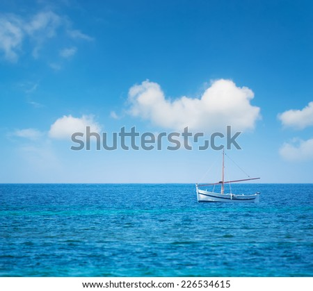a white and blue boat in the blue sea under a cloudy sky - stock photo
