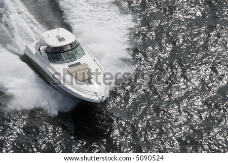 A white and tan speedboat shot from above while travelling fast. - stock photo