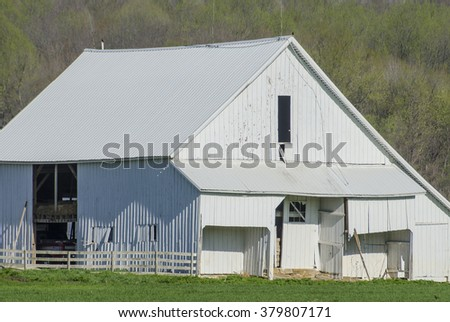 A white barn sits is afield near McAllister's Covered Bridge in Parke County, Indiana