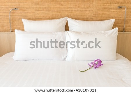 A white bed with 4 pillows and 2 head lights with a flower - stock photo