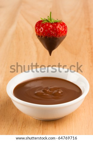 a white bowl containing liquid chocolate with a trawberry just being dipped