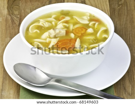 a white bowl filled with Delicious homemade chicken noodle soup - stock photo