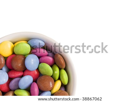 a white bowl full of colorful candy isolated on a white background